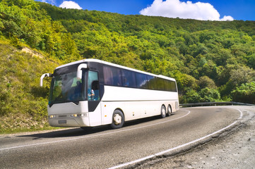 Tourist bus traveling on road among mountains