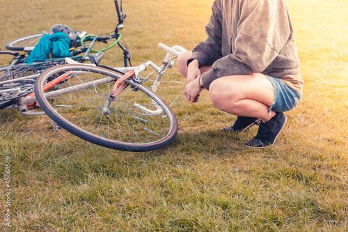 Young woman looking at her bicycle in park