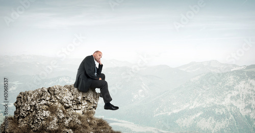 Businessman sitting on a rock in the mountains