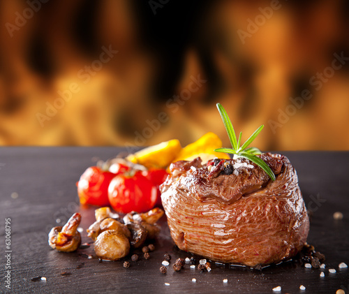 Fresh beef steak on black stone and fire