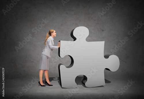 smiling businesswoman pushing big puzzle piece