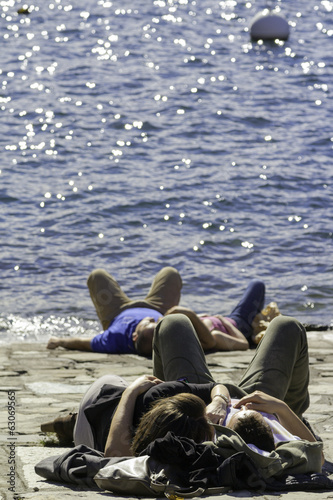Lecco lake-Springtime tourists sunbathing color image