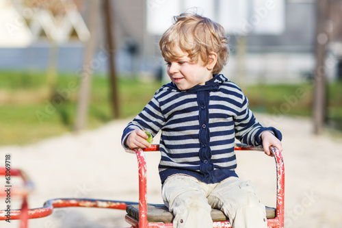 Little toddler boy having fun on old carousel on outdoor playgro
