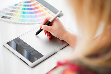 Graphic designer working on a digital tablet and with pantone pa