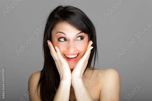 Beautiful surprised woman against a grey background