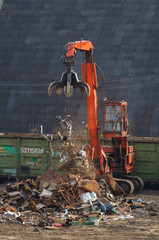 The handler of scrap loads with metal in the car