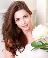 Jolie jeune femme souriante enceinte avec une fleur