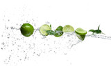 Fototapety Pieces of limes in water splash