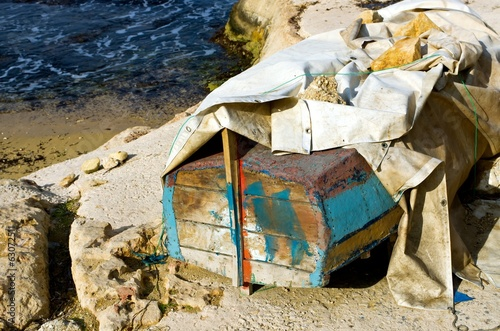 Old boat with a tarp on the beach.