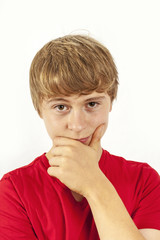 handsome boy in red shirt keeps hand at chin