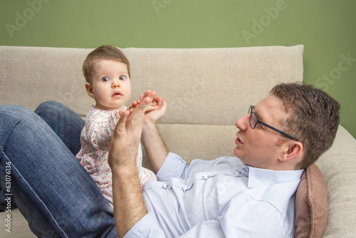 Happy father playing with cute baby in a sofa