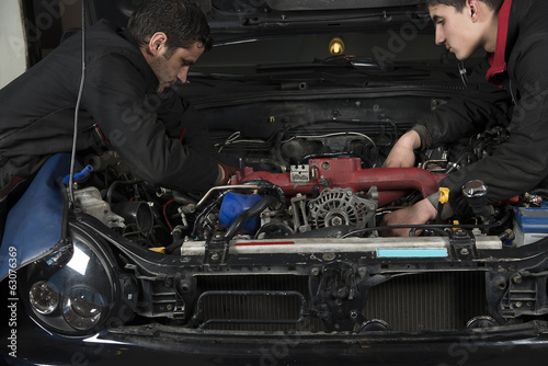 Two auto repairmen fixing a car