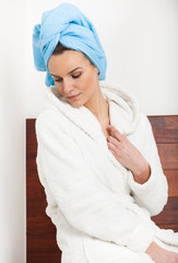 Woman in bathrobe with towel on hairs