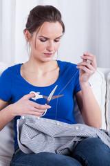 Housewife darning a shirt