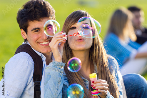 Couple having fun with soap bubbles in the park