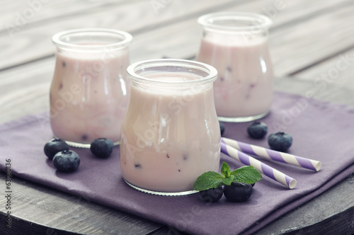 Yogurt with ripe fresh blueberry in jars on wooden background