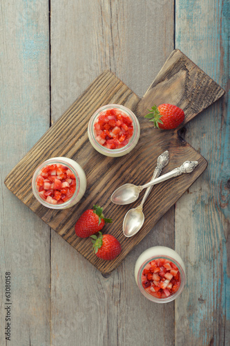 Dessert panna cotta with fresh strawberry on wooden background