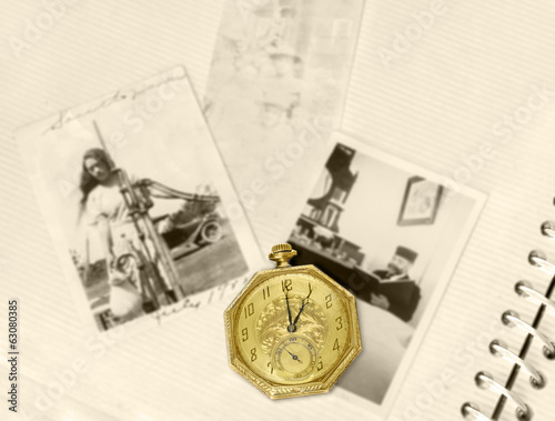 Antique gold pocket watch on vintage photo album.