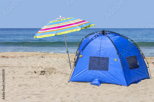 Blue nylon beach tent,multicolored umbrella in the sand.