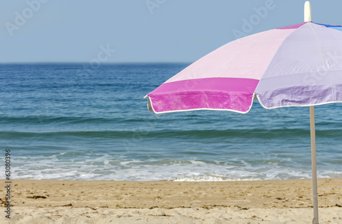 Pink beach umbrella in sand.Ocean and sky background.