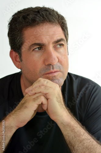 Mature man thinking with hands on chin looking away