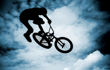 Silhouette of a man doing an jump with a bike.