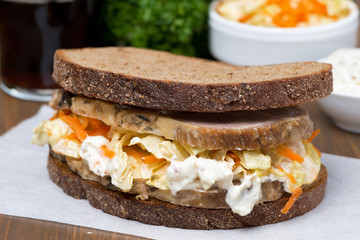 sandwich with coleslaw and baked meat, close-up