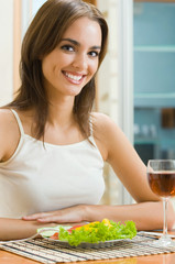 Cheerful woman with glass of redwine and salad