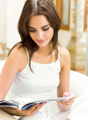 Cheerful young woman reading magazine, indoor