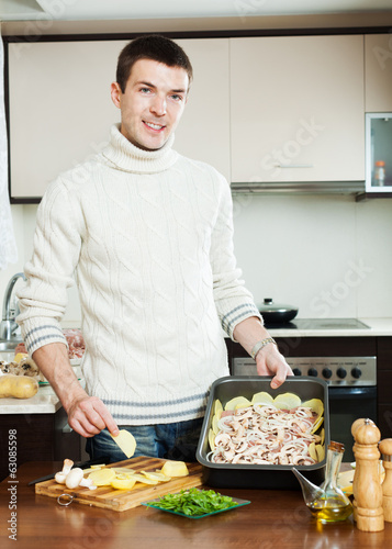 guy cooking meat with mushrooms and potatoes