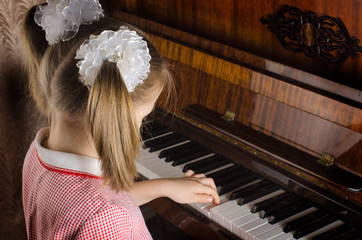 girl learns to play a piano