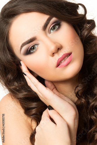 Portrait of young beautiful brunette woman touching her face
