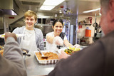 Fototapety Staff Serving Food In Homeless Shelter Kitchen