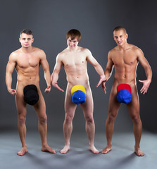 Cheerful naked guys posing in colorful caps