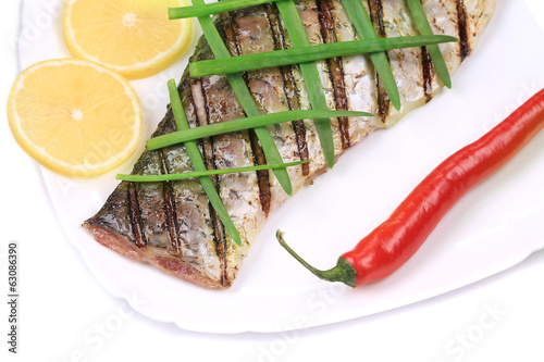 Grilled carp fillet on plate with onion and lemon.