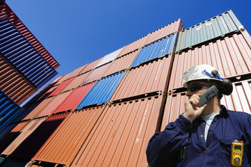 poert worker with stacks of cargo containers