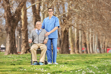 Man in a wheelchair and male nurse posing in park