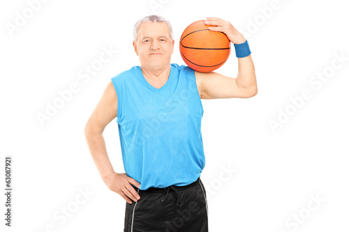Mature man holding a basketball over his shoulder