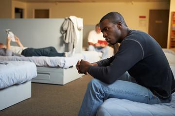 Men Sitting On Beds In Homeless Shelter