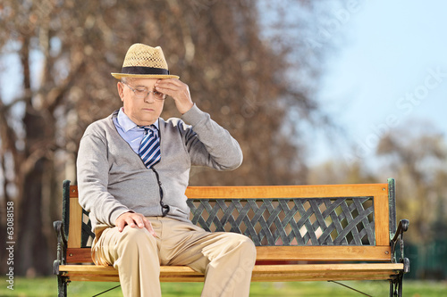 Pensioner with headache sitting on a bench in park