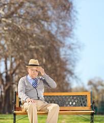 Senior man sitting in park and having a headache