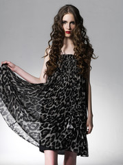 young woman in black dress with brown long ringlets hairs