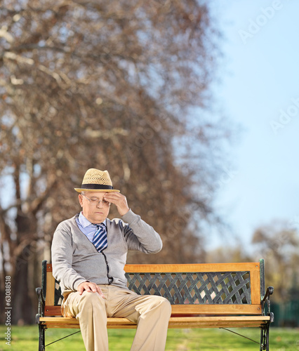 Senior man sitting in park and having a headache