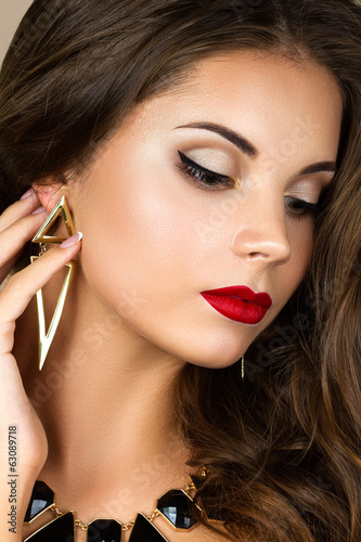 portrait of young brunette woman touching her earring