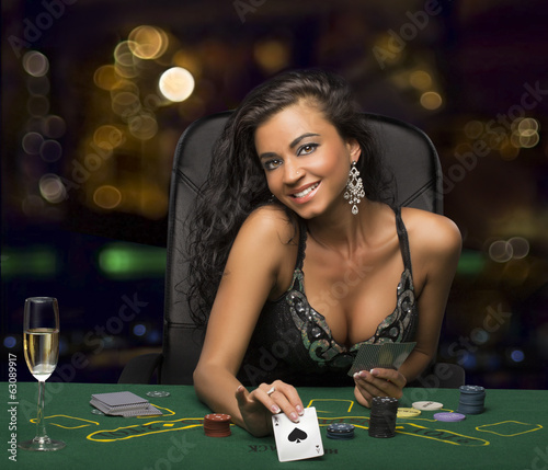 Leinwanddruck Bild brunette girl in the casino playing poker, shows a playing card