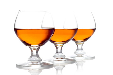 Three glasses of cognac isolated on white
