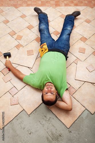 Man resting on ceramic floor tiles he is installing