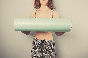 Athletic young woman with foam roller