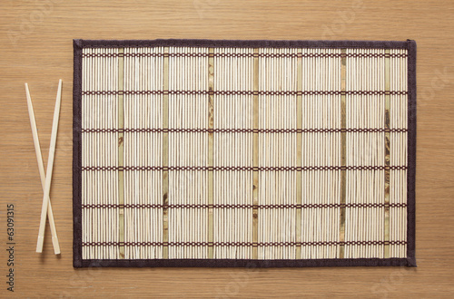Bamboo mat with chopsticks on table