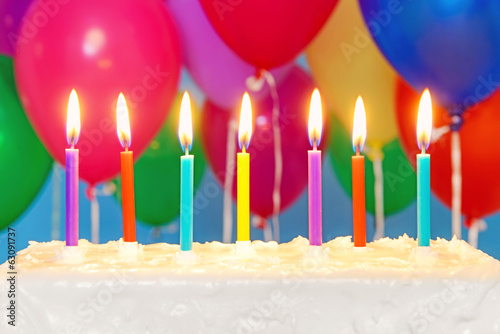Candles on a cake with balloons in background